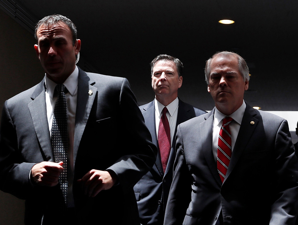 . Former FBI Director James Comey, center, departs after an open Senate Intelligence Committee hearing, to head to a closed session, on Capitol Hill, Thursday, June 8, 2017, in Washington. (AP Photo/Alex Brandon)