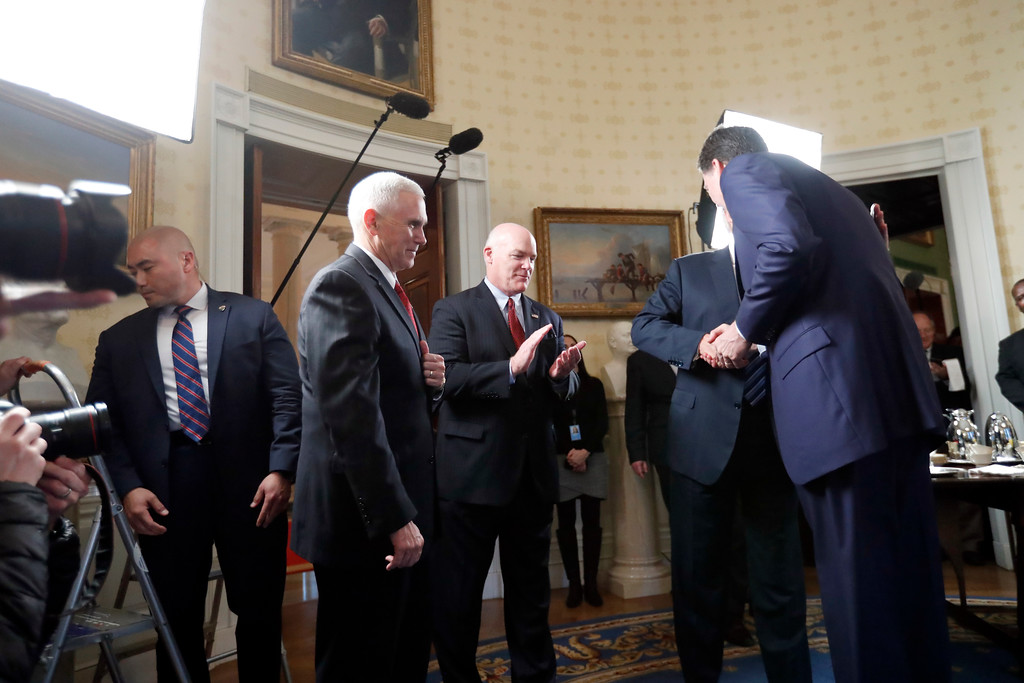 . Vice President Mike Pence, second from left, and Secret Service Director Joseph Clancy stand as President Donald Trump hugs FBI Director James Comey during a reception for inaugural law enforcement officers and first responders in the Blue Room of the White House, Sunday, Jan. 22, 2017 in Washington. (AP Photo/Alex Brandon)