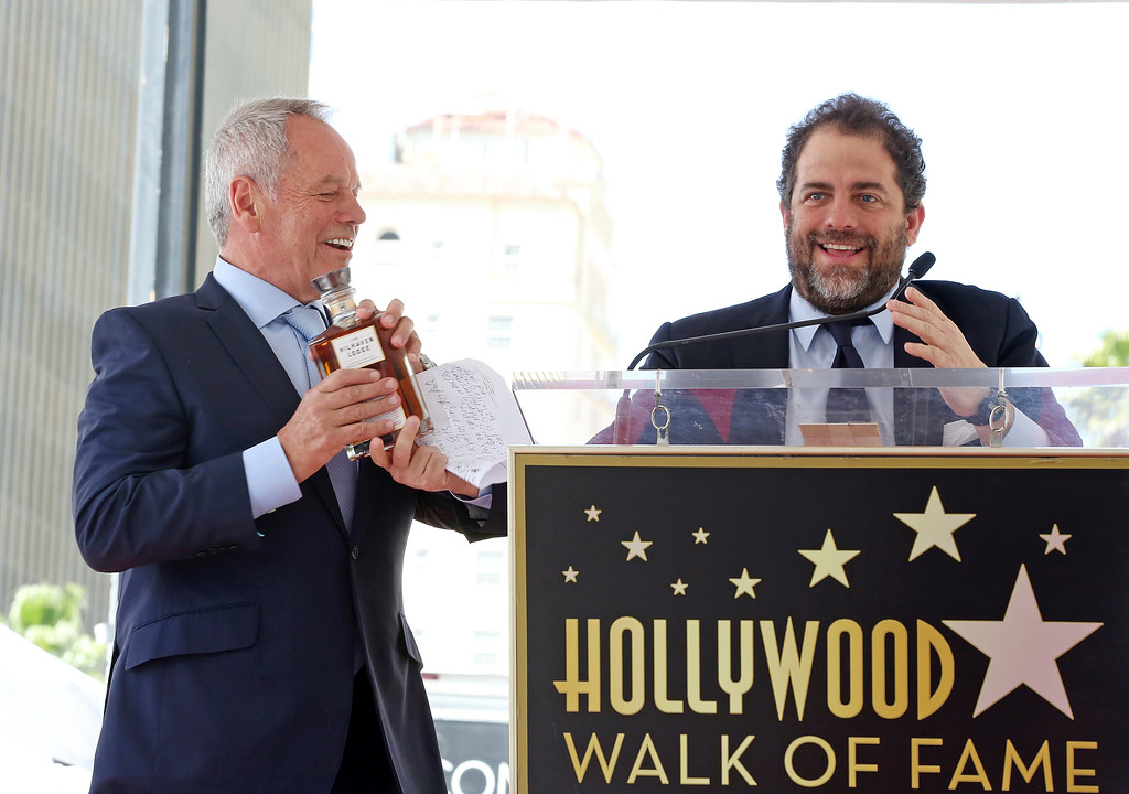 . Director Brett Ratner hands celebrity chef Wolfgang Puck a bottle of The Hilhaven Lodge whiskey at a ceremony honoring Puck with a star on the Hollywood Walk of Fame, Wednesday, April 26, 2017, in Los Angeles.  (AP Photo/Reed Saxon)