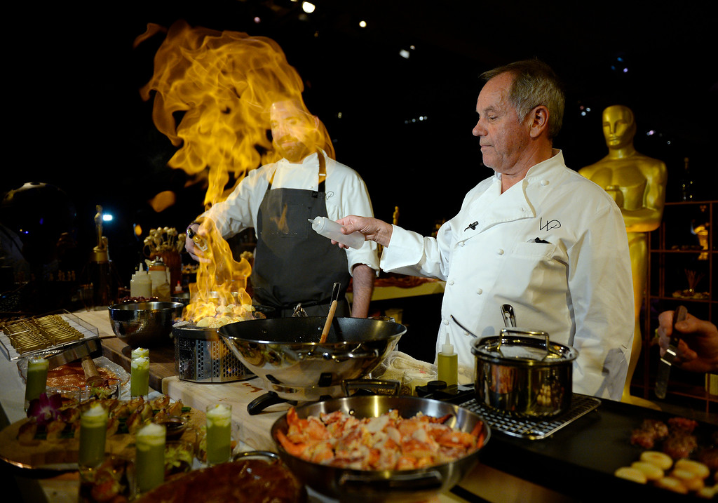 . HOLLYWOOD, CA - FEBRUARY 18: Master chef Wolfgang Puck (C) prepares samples from the menu for display during the 88th Annual Academy Awards Governors Ball press preview at The Ray Dolby Ballroom at Hollywood & Highland Center on February 18, 2016 in Hollywood, California.(Photo by Kevork Djansezian/Getty Images)