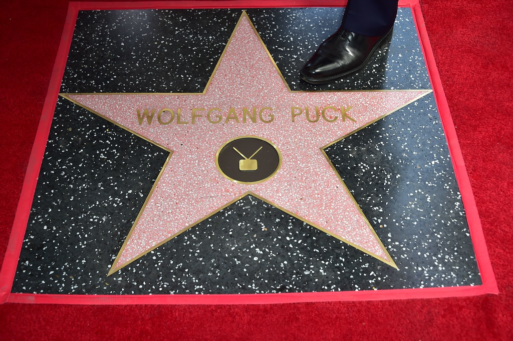 . Celebrity chef Wolfgang Puck puts his foot on the star at his Walk of Fame Star ceremony in Hollywood, California on April 26, 2017 where he was the recipient of the 2,608 Star in the category of Television. (FREDERIC J. BROWN/AFP/Getty Images)