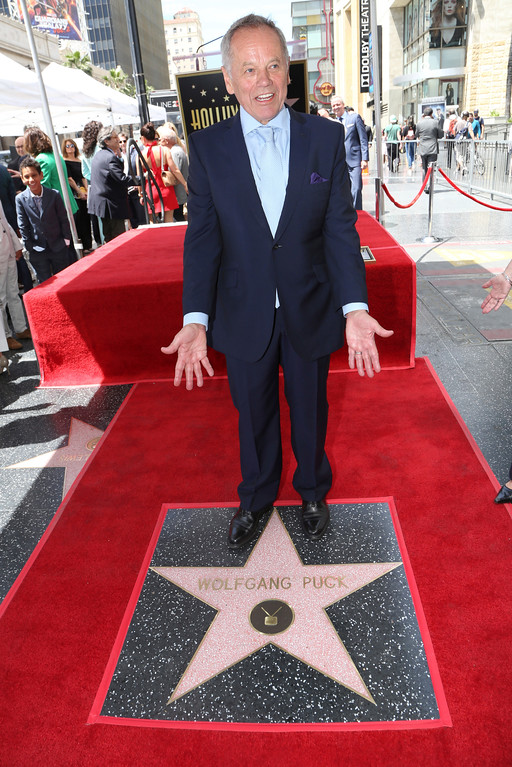 . Celebrity chef Wolfgang Puck stands on his star on the Hollywood Walk of Fame during presentation ceremonies Wednesday, April 26, 2017, in Los Angeles. The star is in front of the Hollywood and Highland complex, home of the annual Oscars show, whose Governors Ball Puck has catered for years. (AP Photo/Reed Saxon)