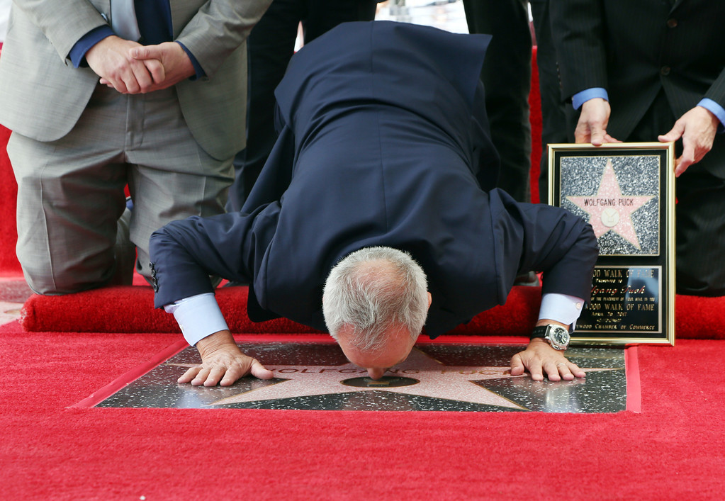 . Celebrity chef Wolfgang Puck kisses his star on the Hollywood Walk of Fame during presentation ceremonies Wednesday, April 26, 2017 in Los Angeles. The star in the category of Television is in front of the Hollywood and Highland complex, home of the annual Oscars show, whose Governors Ball Puck has catered for years. (AP Photo/Reed Saxon)