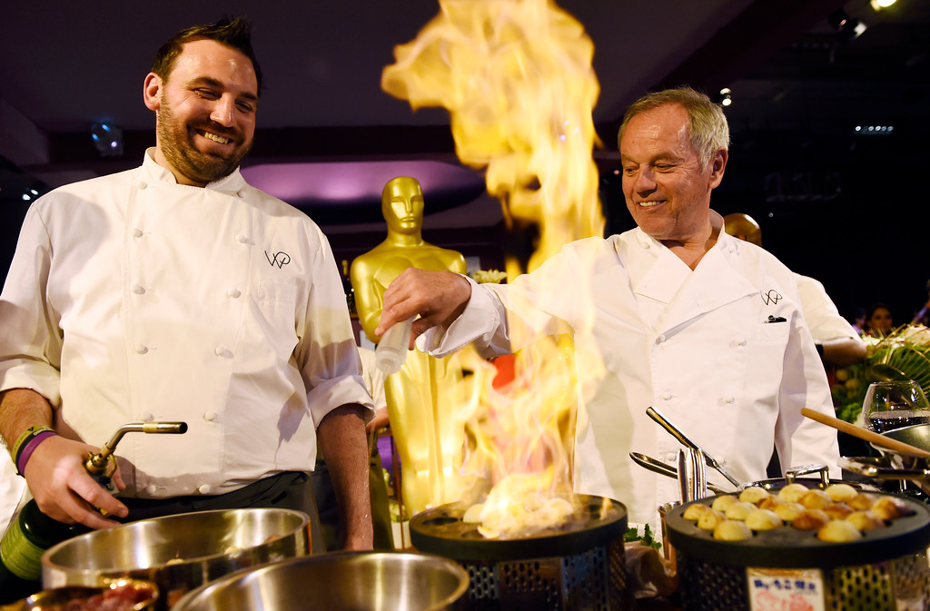 . Governors Ball Master Chef Wolfgang Puck, right, and pastry chef Tyler Atwell pour a raspberry liqueur on donuts during the 88th Academy Awards Governors Ball Press Preview on Thursday, Feb. 18, 2016, in Los Angeles. The 88th Academy Awards ceremony will be held at the Dolby Theatre on Sunday, Feb. 28. (Photo by Chris Pizzello/Invision/AP)