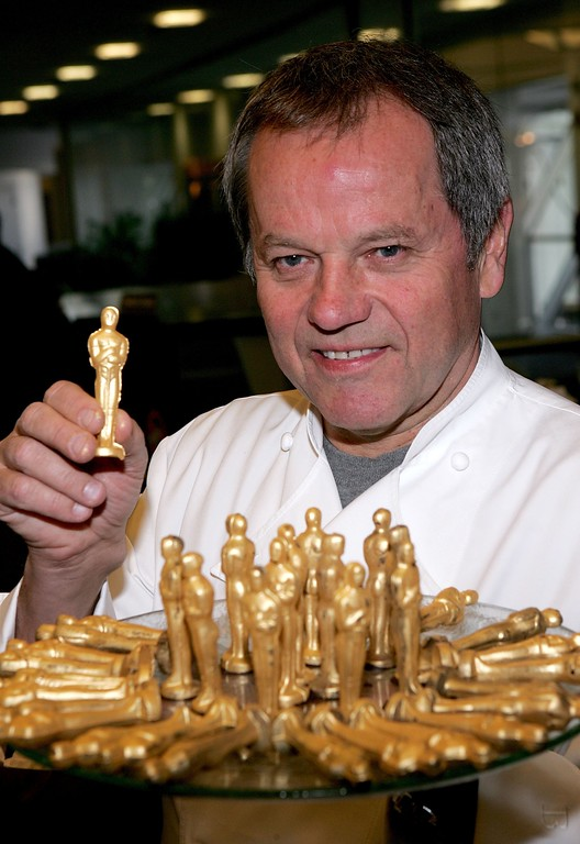 """. NEW YORK - FEBRUARY 02:  Chef Wolfgang Puck holds a chocolate mini Oscar during a media conference after newly minted Oscar statuettes were loaded onto United Flight 23, also known as \""""Oscar-1\"""" to Los Angeles, at John F. Kennedy (JFK) International Airport February 2, 2006 in New York City.  (Photo by Paul Hawthorne/Getty Images)"""