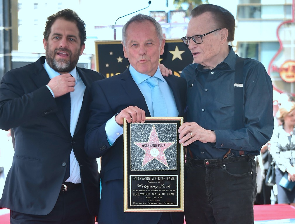 . Celebrity chef Wolfgang Puck poses on his just unveiled Star with Director Brett Ratner (L) and television personality Larry King (R) at Puck\'s Walk of Fame Star ceremony in Hollywood, California on April 26, 2017 where he was the recipient of the 2,608 Star in the category of Television. (FREDERIC J. BROWN/AFP/Getty Images)