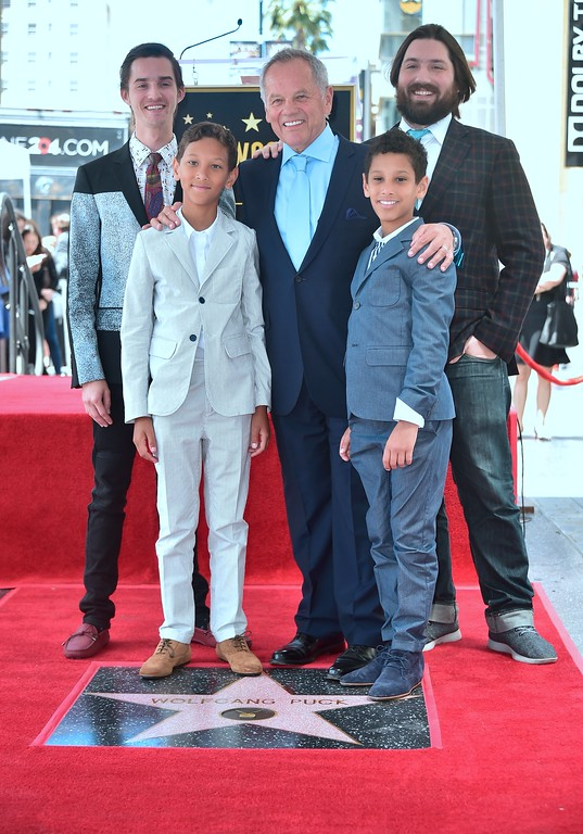 . Celebrity chef Wolfgang Puck poses with his sons on his just unveiled Star at his Walk of Fame Star ceremony in Hollywood, California on April 26, 2017 where he was the recipient of the 2,608 Star in the category of Television. (FREDERIC J. BROWN/AFP/Getty Images)
