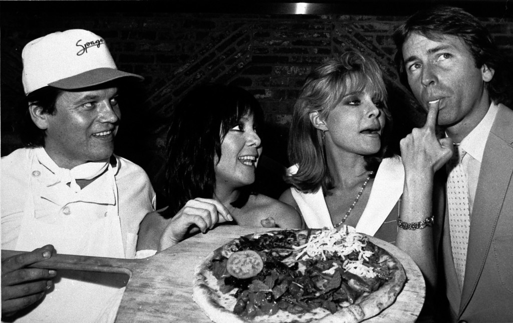 """. Chef Wolfgang Puck, owner of Spago Restaurant, holds a pizza as cast members of the TV sitcom \""""Three\'s Company\"""" sample it, Sept. 19, 1983, during a celebration launching the series\' eighth season.  From left:  Puck, Joyce DeWitt, Priscilla Barnes, and John Ritter.  (AP Photo/Joan Adlen)"""