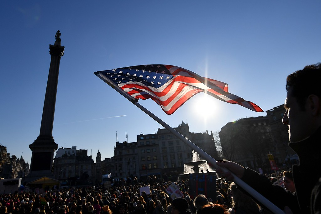 """. A protester waves the US flag during the Women\'s March in Trafalgar Square in London on January 21, 2017 as he joins thousands of others as part of a global day of protests against new US President Donald Trump. Thousands of people marched through central London on January 21 as part of a global day of protests against new US President Donald Trump and his derogatory remarks about women. The largely female crowd, which also had many men and children, marched from the US embassy to Trafalgar Square, chanting \""""dump Trump\"""" and waving banners demanding equal rights. (BEN STANSALL/AFP/Getty Images)"""