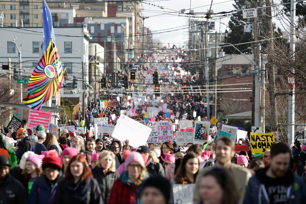 """. People march down South Jackson Street during the Women\'s March in Seattle, Washington on January 21, 2017.  Led by women in pink \""""pussyhats,\"""" hundreds of thousands of people packed the streets of Washington and other cities Saturday in a massive outpouring of defiant opposition to America\'s hardline new president, Donald Trump.(JASON REDMOND/AFP/Getty Images)"""