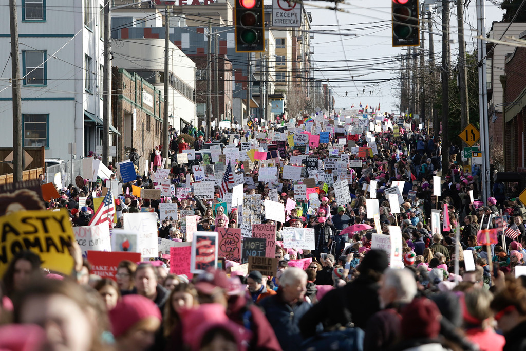 """. People march down South Jackson Street during the Women\'s March in Seattle, Washington on January 21, 2017.  Led by women in pink \""""pussyhats,\"""" hundreds of thousands of people packed the streets of Washington and other cities Saturday in a massive outpouring of defiant opposition to America\'s hardline new president, Donald Trump. (JASON REDMOND/AFP/Getty Images)"""