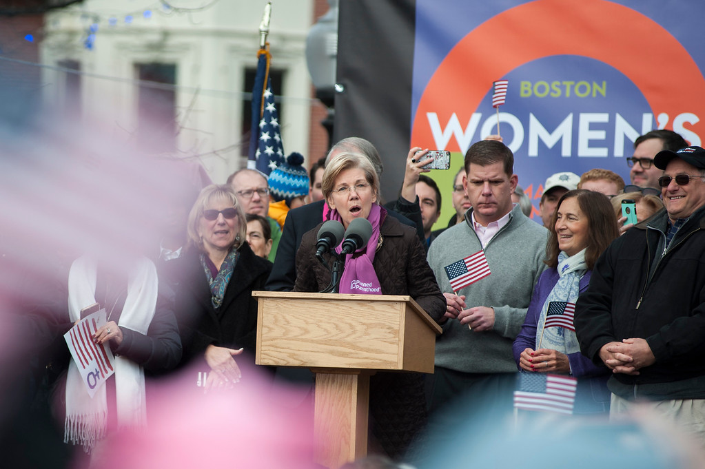 """. US Senator Elizabeth Warren speaks before a march across Boston Commons during the Boston Women\'s March on January 21, 2017.  Led by women in pink \""""pussyhats,\"""" hundreds of thousands of people packed the streets of Washington and other cities Saturday in a massive outpouring of defiant opposition to America\'s hardline new president, Donald Trump. (RYAN MCBRIDE/AFP/Getty Images)"""