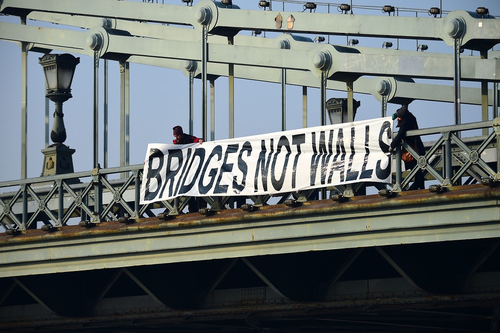 . Participants hold a banner \'Bridges not  walls\' on Lanchid (Chain Bridge) in Budapest downtown on January 21, 2017 during a women protesters march in a rally against US President Donald Trump following his inauguration.  A Women\'s March kicked off, the first of a series of global protests in defence of women\'s rights, as demonstrators rally against Donald Trump, who was sworn in as the 45th president of United States on January 20. (ATTILA KISBENEDEK/AFP/Getty Images)