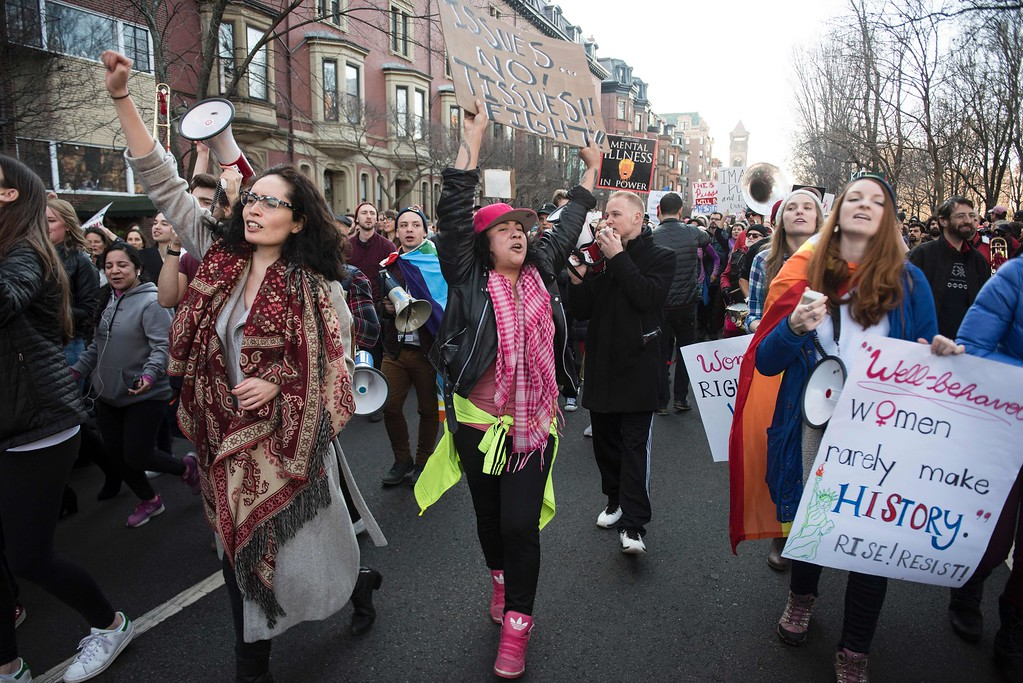 """. Protesters march across Boston Commons during the Boston Women\'s March for America on January 21, 2017.  Led by women in pink \""""pussyhats,\"""" hundreds of thousands of people packed the streets of Washington and other cities Saturday in a massive outpouring of defiant opposition to America\'s hardline new president, Donald Trump. / AFP / Ryan McBride        (Photo credit should read RYAN MCBRIDE/AFP/Getty Images)"""