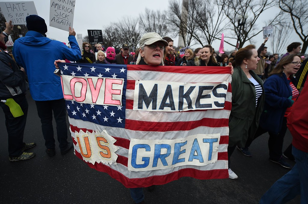 . Protesters march in Washington, DC, during the Womens March on January 21, 2017.  Hundreds of thousands of people flooded US cities Saturday in a day of women\'s rights protests to mark President Donald Trump\'s first full day in office. (ROBYN BECK/AFP/Getty Images)