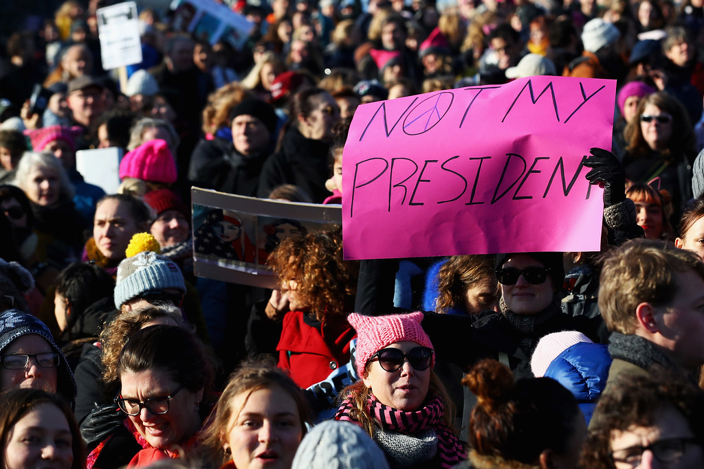 """. AMSTERDAM, NETHERLANDS - JANUARY 21:  Demonstrators with a sign saying \"""" Not my President \"""" make their way from the iamsterdam statue in front of the Rijksmuseum towards US Consulate during the Women\'s March held at Museumplein on January 21, 2017 in Amsterdam, Netherlands.  The Women\'s March originated in Washington DC but soon spread to be a global march calling on all concerned citizens to stand up for equality, diversity and inclusion and for women\'s rights to be recognised around the world as human rights. Global marches are now being held, on the same day, across seven continents.  (Photo by Dean Mouhtaropoulos/Getty Images)"""