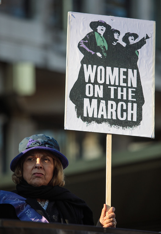 . LONDON, ENGLAND - JANUARY 21: A protester dressed as a suffragette holds a placard outside the US Embassy in Grosvenor Square ahead of the Women\'s March on January 21, 2017 in London, England. The Women\'s March originated in Washington DC but soon spread to be a global march calling on all concerned citizens to stand up for equality, diversity and inclusion and for Women\'s rights to be recognised around the world as human rights. Global marches are now being held, on the same day, across seven continents. (Photo by Jack Taylor/Getty Images)
