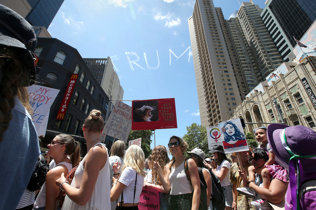 """. Thousands file through the streets during the Women\'s March protesting the start of Donald Trump\'s presidency as a skywriting plane spells out \""""Trump\"""" above in Sydney, Australia, Saturday, Jan. 21, 2017. Protesters at the Women\'s March rally carried placards with slogans including \""""Women of the world resist,\"""" \'\'Feminism is my trump card\"""" and \""""Fight like a girl.\"""" (AP Photo/Rick Rycroft)"""