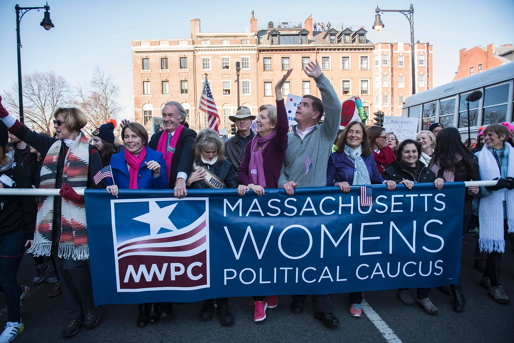 """. US Senator Elizabeth Warren (C) and Boston Mayor Marty Walsh (C R)march with protestors across Boston Commons during the Boston Women\'s March for America on January 21, 2017.  Led by women in pink \""""pussyhats,\"""" hundreds of thousands of people packed the streets of Washington and other cities Saturday in a massive outpouring of defiant opposition to America\'s hardline new president, Donald Trump. / AFP / Ryan McBride        (Photo credit should read RYAN MCBRIDE/AFP/Getty Images)"""