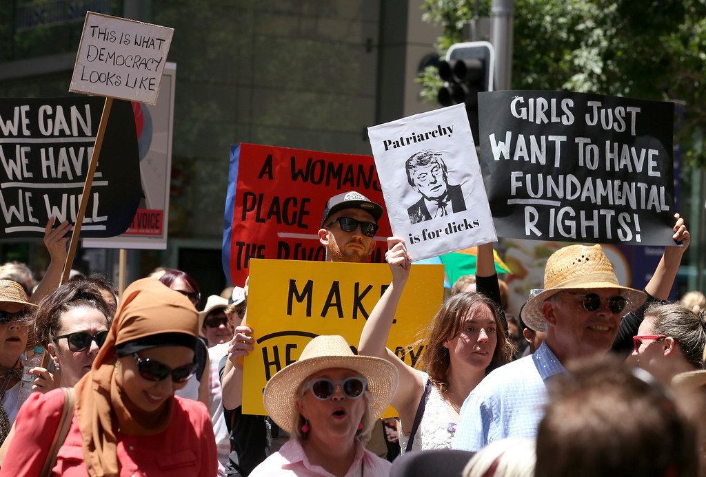 """. People file through the streets with placards during the Women\'s March against the start of Donald Trump\'s presidency, in Sydney, Australia, Saturday, Jan. 21, 2017. Protesters at the Women\'s March rally carried placards with slogans including \""""Women of the world resist,\"""" \'\'Feminism is my trump card\"""" and \""""Fight like a girl.\"""" (AP Photo/Rick Rycroft)"""