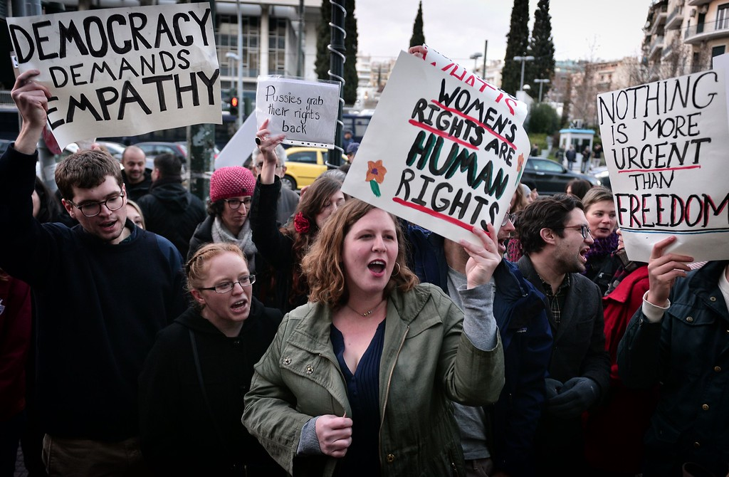 . US Nationals hold placards and chant slogans during an demonstration in front of the US embassy in Athens on January 21, 2017, in solidarity with the Women\'s March on Washington, one day after the inauguration of Donald Trump as US President.  Protest rallies were held in over 30 countries around the world in solidarity with the Washington Women\'s March in defense of press freedom, women\'s and human rights following the official inauguration of Donald J Trump as the 45th President of the United States of America. (LOUISA GOULIAMAKI/AFP/Getty Images)