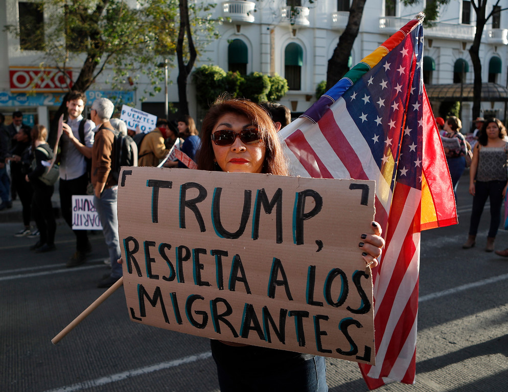 """. A woman holds a sign that reads  in Spanish \""""Trump, respect migrants\"""" during a march called by a local women\'s movement against U.S. President Donald Trump in Mexico City, Friday, Jan. 20, 2017. Donald Trump became the 45th president of the United States Friday, Jan. 20 2017, amid apprehension in Mexico regarding his previous comments about Mexico and his promise to build a border wall to halt migration. (AP Photo/Eduardo Verdugo)"""