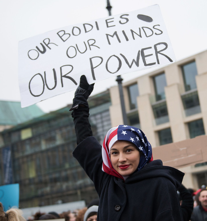 . BERLIN, GERMANY - JANUARY 21: A Woman wearing a USA flag as a headscarf attends a protest for women\'s rights and freedom in solidarity with the Women\'s March on Washington in front of Brandenburger Tor on January 21, 2017 in Berlin, Germany. The Women\'s  March originated in Washington DC but soon spread to be a global march calling on all concerned citizens to stand up for equality, diversity and inclusion and for Women\'s  rights to be recognised around the world as human rights. Global marches are now being held, on the same day, across seven continents. (Photo by Steffi Loos/Getty Images)