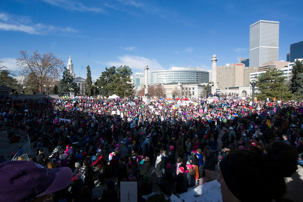 """. Demonstrators gather at Civic Center Park in Denver, Colorado during the Women\'s March on January 21, 2017.  Led by women in pink \""""pussyhats,\"""" hundreds of thousands of people packed the streets across the US Saturday in a massive outpouring of defiant opposition to America\'s hardline new president, Donald Trump. (JASON CONNOLLY/AFP/Getty Images)"""