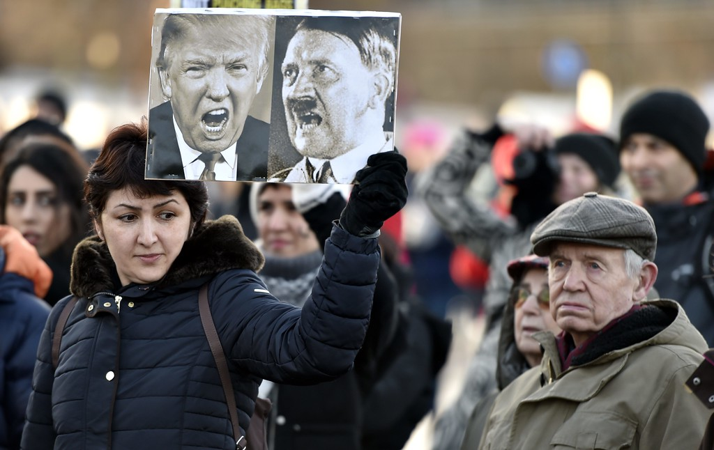 . A participant of a Women\'s March in Helsinki holds up a poster depicting US President Donald Trump and German dictator Adolf Hitler on January 21, 2017, one day after the US president\'s inauguration. (JUSSI NUKARI/AFP/Getty Images)