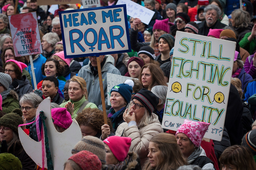 """. Jen Desloges of Plymouth whistles while holding a \""""hear me roar\"""" sign during the during the New Hampshire Women\'s Day of Action and Unity rally in front of the State House in Concord, N.H., on Saturday, Jan. 21, 2017. (Elizabeth Frantz/Concord Monitor via AP)"""