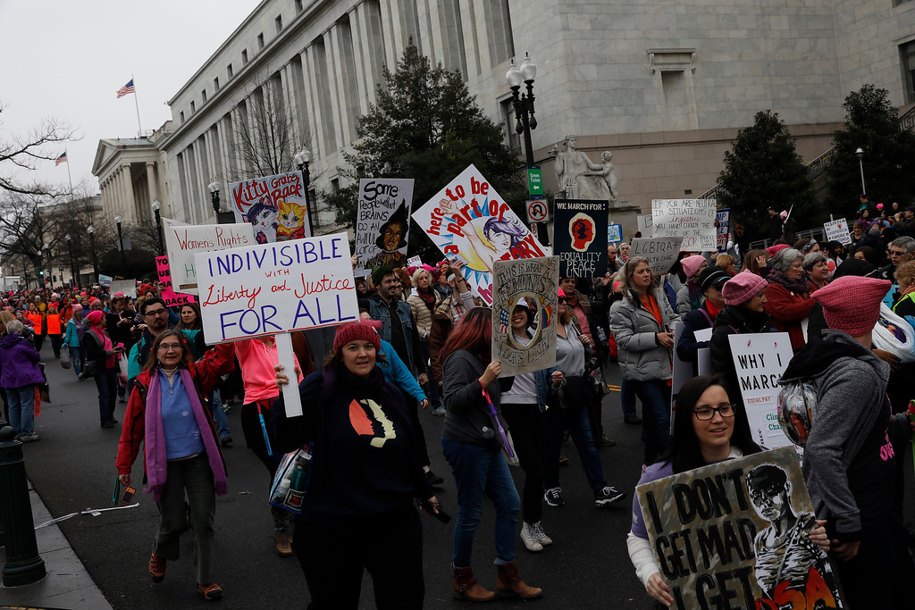 . WASHINGTON, DC - JANUARY 21: Protesters march past the Rayburn House Office Building during the Women\'s March on Washington January 21, 2017 in Washington, DC. The march is expected to draw thousands from across the country to protest newly inaugurated President Donald Trump. (Photo by Aaron P. Bernstein/Getty Images)