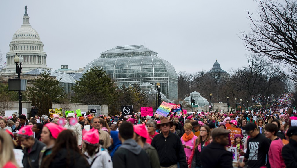 . Demonstrators march past the US Capitol (L) on the National Mall in Washington, DC, for the Women\'s march on January 21, 2017. Hundreds of thousands of protesters spearheaded by women\'s rights groups demonstrated across the US to send a defiant message to US President Donald Trump. (JIM WATSON/AFP/Getty Images)