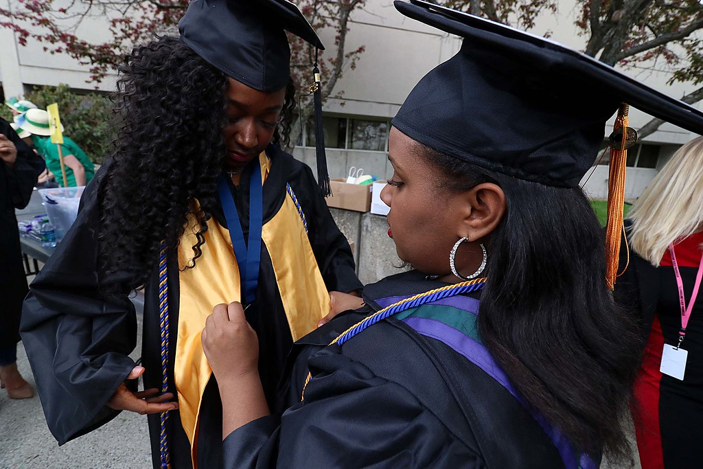. Mount Wachusett Community College held its fifty-third commencement on Wednesday, May 16, 2018. Shantel Woodson from Lunenburg, on right, helps Naomi Tucker of Leominster get ready as they both prepare to graduate. SENTINEL & ENTERPRISE/JOHN LOVE