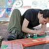 Student Jonathan Burgos, 24, helps paint the wood for the new seats that were being put in on Main Street in Fitchburg by Mount Wachusett Community College's First Year Experience Class (FYE). SENTINEL & ENTERPRISE/JOHN LOVE
