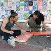 Students Brenda Calderon, 28, and Jonathan Burgos, 24, help paint the wood for the new seats that were being put in on Main Street in Fitchburg by Mount Wachusett Community College's First Year Experience Class (FYE). SENTINEL & ENTERPRISE/JOHN LOVE