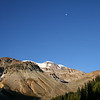 A DAYTIME MOON ABOVE THE SUMMIT OF MOUNT RAINIER