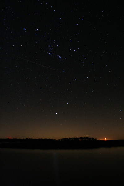 ORION, LEPUS, AND CANIS MAJOR IN THE NIGHT SKY OVER THE GULF OF MEXICO ON AN ISLAND NEAR CEDAR KEY, FLORIDA. THE LIGHT AT THE HORIZON IS THE CRYSTAL RIVER NUCLEAR PLANT. THE STREAK IS EITHER A SHOOTING STAR OR A JET FLYING BY.