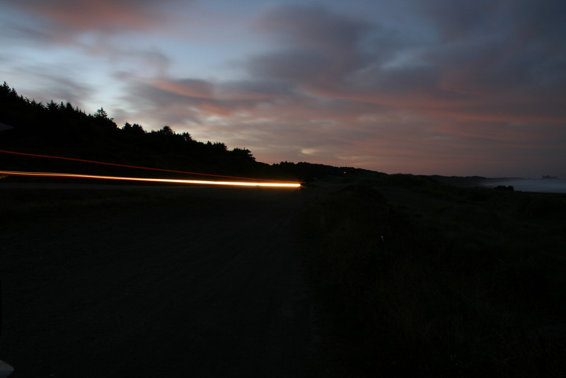 A CAR GOES BY ON THE PACIFIC COAST HIGHWAY AT TWILIGHT