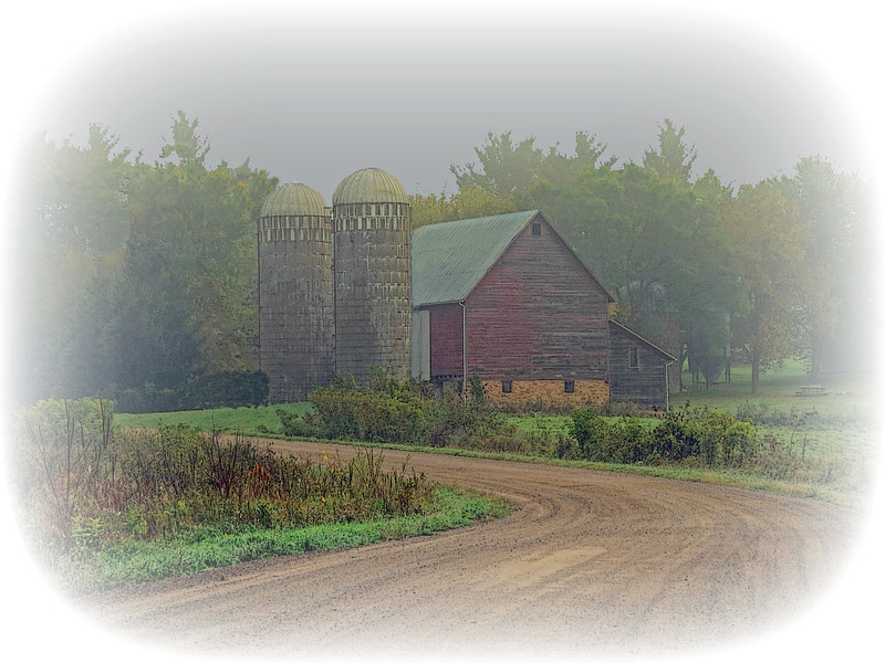 OLD BARN WITH GREEN ROOF ALONG DIRT ROAD