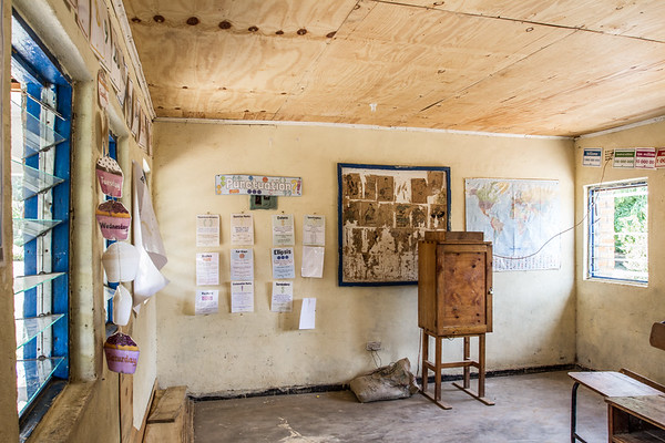 Inside an empty classroom.  Many time, there are hundreds of students to a single teacher.  Well paid teachers in rural areas can earn a professional wage close to $250 per year.