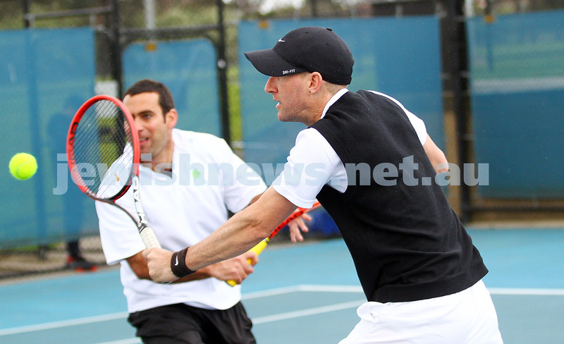 29-8-15. Maccabi Tennis. Semi final played at the Leon Haskin. Assaf Drori plays a volley with Asaf Nagar looking on. Photo: Peter Haskin