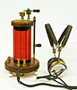 Crystal Set - by VE6AB<br /> <br /> My crystal radio receiver, also called a crystal set or cat's whisker receiver, is a very simple radio receiver, popular in the early days of radio. It needs no battery or power source and runs on the power received from radio waves by a long wire antenna. It gets its name from its most important component, the crystal detector as seen on the top of my crystal set. The detector cup has a piece of galena crystal in it.<br /> <br /> My version of a early crystal radio was built in my shop, with the coil form turned in the lathe, and then had the thermaleze magnet wire wound in the lathe as well. All the brass parts including the detector up top were machined in my shop also. The slider on the side is used for tuning stations, and then may be locked. The top and bottom are made from walnut. the feet are drawer-pulls from Home-Depot. All wiring is hidden inside of the coil-form. The head-phones are vintage 1924 Brandies that I found on the Internet. The set is a very good performer, and is a joy to use.