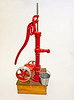 """This model of a early well pump is fully operational with the pick-up located below the wooden platform, where a pan of water is placed for demonstration purposes. I had the castings poured in a local foundry, from wooden patterns that I made in my shop. The model pumps water with the actual pump handle being used, although as you can see in my photo, I built the additional pump-jack that is clamped in place at the bottom of the pump housing. In days gone by, the pump-jack would have been belted to a Hit & Miss gasoline engine, when large amounts of water had to be pumped. If the pump-jack was being used, the pump-handle would have been replaced with a pair of wooden arms, connecting the pump-jack to the pump. Anyone that sees this model gets a bigger kick out of the pail (galvanized of-course) that I built to pump water into, than the actual pump itself. The model stands about 18"""" high."""