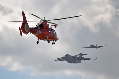 HH-65 landing while C-17 and C-47 fly past in formation.