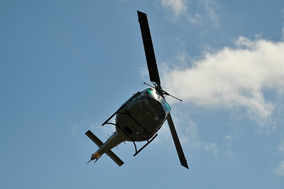 UH-1 Huey banks overhead.
