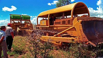 Around 1986 an on farm demonstration was arranged of the amazing Homan blade plow which slices a huge steel arrow shaped blade app. a foot or so below the surface to cut the roots of problem re-growth 'suckers' of mainly brigalow type. The green hoppers up top deposit grass seeds into the void left into which any rain and run off will penetrate. Production is raised.