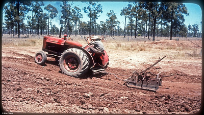 Brian (Lofty) is working for a farmer (Vince Janke) digging a small water dam on his property. Not exactly an earthmoving machinery setup. An old tractor, a 'tumbling tommy' scoop and an old mulboard plow to work as our ripper. Well we dug a bit of a dam and had a lot of fun. He was a funny guy to work for/with. Was just a casual job for me between the wool sheds way out west.