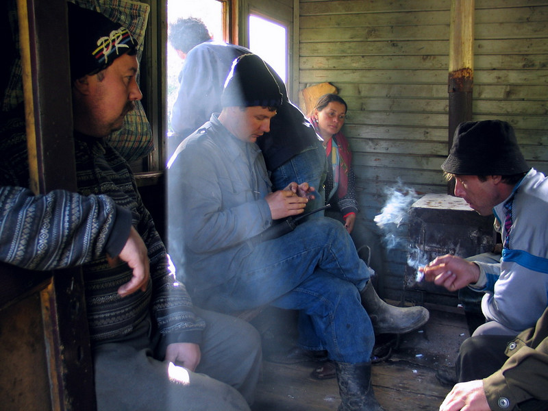 "In the ""passenger car"" (in fact a half of a caboose, the other half being a tender) the train crew (chief and brakemen) share the room and the stowe for baking potatoes with casual passengers met on the way. Valea Novatului, Viseul de sus, Maramures, Romania, 2004<br /> This is the last narrow gauge steam traction railway in Europe"