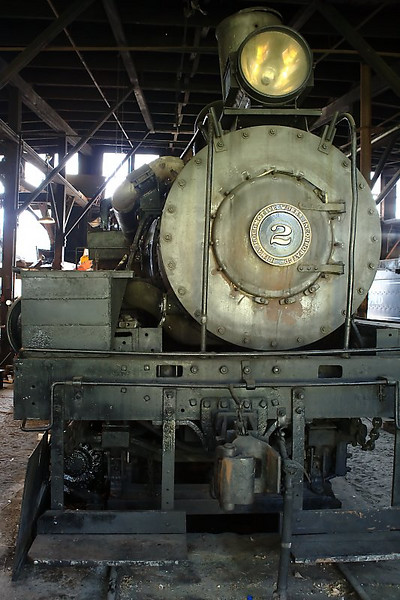"""The engineer explained to me that this was a """"Shay"""" type locomotive, which is why the boiler is off to the right, rather than being centered between the wheels.  Whereas most steam locomotives drive the wheels on both sides evenly, this one just drives the ones on the left (in this photo).  The boiler is moved to the right to make the weight balance evenly between left and right."""