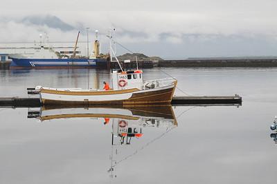 Bateau de pêche dans le port de Reikjavik-Islande. Au fond un gros chalutier bleu et devant un petit bâteau qui prend des pêcheurs qui pêche avec une cane.